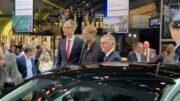 Symbol der Lage - Mini Mitarbeiter schauen der Opel Präsentation zu.